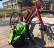 Photo of Ashley's dark red commuter bike and green backpack.