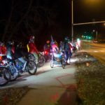 Group of bicycle riders, some dressed as santas, wait to cross a street in the dark.
